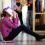 Ung tjej sitter på golvet i skolkorridor.