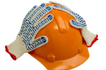 Arbetshandskar tar sig för huvudet över en skyddshjälm.
