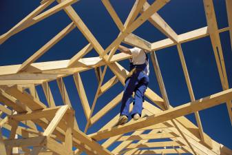 En bild på en byggarbetare som klättrar i vad som ser ut som taket på ett högt obyggt hus. Bilden är tagen underifrån.