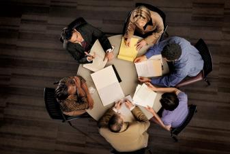 Sex personer som sitter runt ett bord, sett uppifrån.