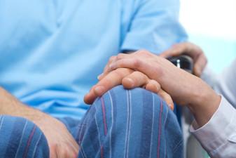 En bild på två personers händer. Den ena personen sitter i rullstol och den andra personens hand vilar på den rullstolsburnes hand.