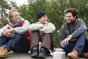 Tre män som verkar vara vänner sitter på en klippa i naturen. De ser glada ut.