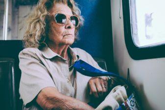 Äldre kvinna med solglasögon i kollektivtrafiken