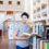 Ung man står med uppfälld bok i bibliotiek