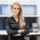 Kvinna med armarna i kors på sin arbetsplats