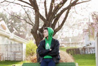 Ung man med armarna i kors, sitter på ryggstödet till parkbänk