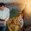 Pappa arbetar på laptop med sovande barn bredvid sig i soffan