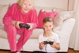 Äldre kvinna spelar tv-spel med barnbarn