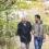 En äldre och en yngre man går arm i arm på en stig