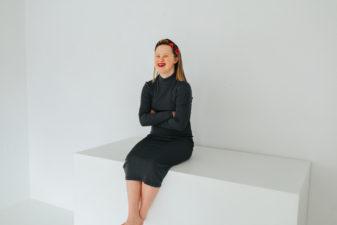 Ung kvinna med downs syndrom sitter med armarna i kors och ler