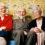 En äldre man och två äldre kvinnor skrattar tillsammans i soffa