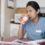Trött sjuksköterska dricker kaffe i personalrummet