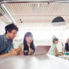 Två kollegor sitter med en laptop på en arbetsplats