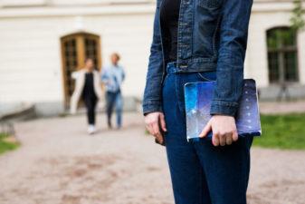 Flicka med bok i handen på skolgård