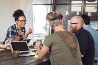 Tre kollgor sitter vid ett bord och samtalar glatt