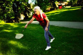 Äldre kvinna som spelar badminton på en gräsmatta.
