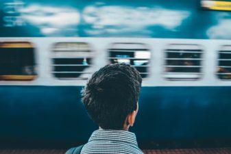 Korthårig person står och väntar på ett tåg.