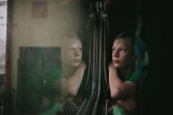 Barn tittar ut genom tågfönster