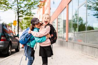 Glada skolbarn håller om varandra på gatan