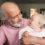 Äldre man håller barnbarn i famnen