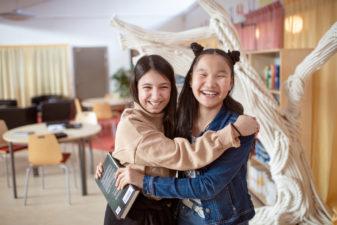 Två unga tjejer håller om varandra i skolmiljö