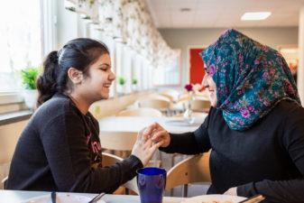Två flickor skrattar med varandra i skolmatsalen