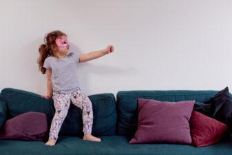 Flicka leker superhjälte i soffan