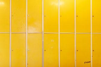Skåp i skolkorridor. På ett av skåpen har någon skrivit