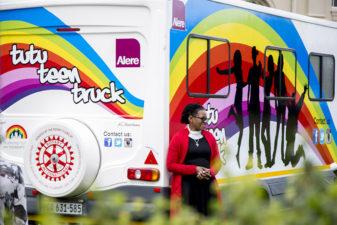 Kvinna står utanför den regnbågdsfärgade bussen Tutu Teen Truck