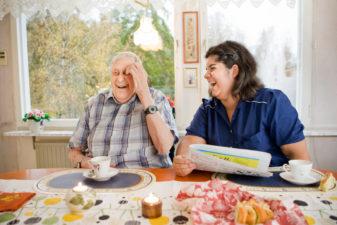 Äldre man och kvinna från hemtjänst skrattar tillsammans