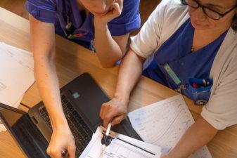 Två sjuksköterskor jobbar ihop framför datorn
