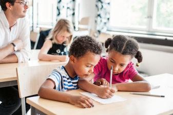 En pojke och en flicka hjälps i skolan