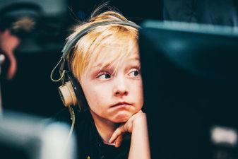 Pojke med hörlurar sitter framför datorskärm