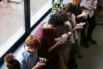 Flera personer står bredvid varandra och tittar i mobilen