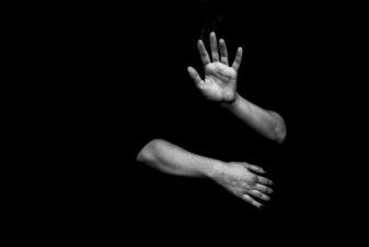 Person som håller upp händerna som för att skydda sig själv