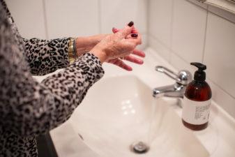 Äldre kvinna tvättar händerna