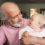 Older man holding grandchild and smiling